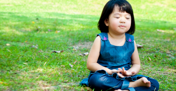 A little girl meditating on a lawn | Buump Active's guide to easy mindfulness